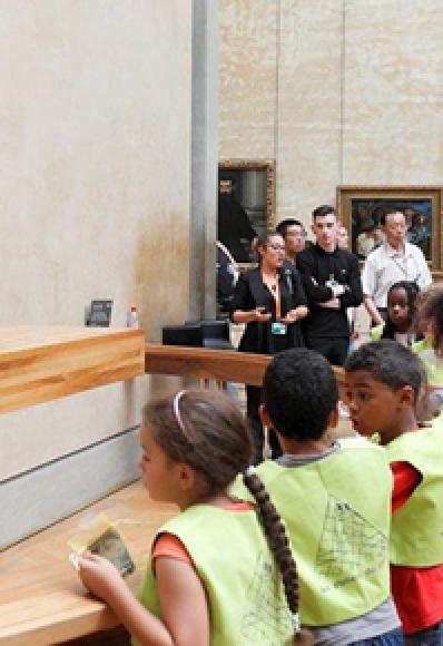 Enfants et adultes dans une salle du musée