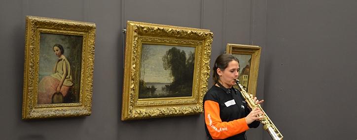 Etudiante jouant de la clarinette devant une oeuvre