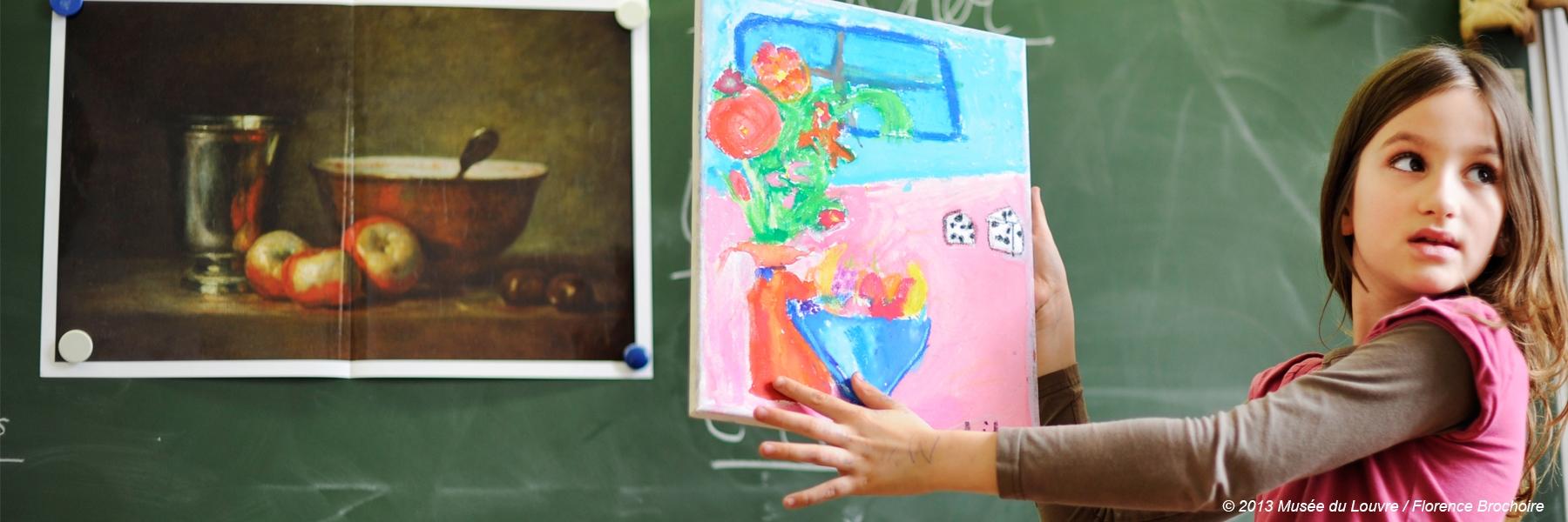 Photographie d'une élève en classe montrant sa production plastique